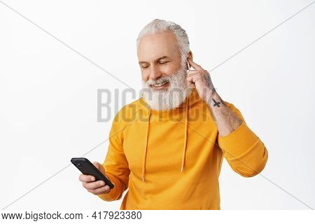 Happy Old Guy With Tattoos Listen Music On Smartphone With Wireless Headphones. Senior Hipster Put E