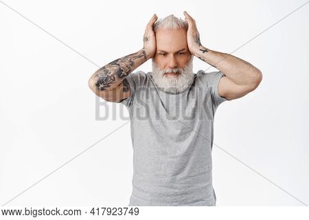 Annoyed And Distressed Old Man With Tattoos, Holding Hands On Head With Troubled Upset Face, Looking