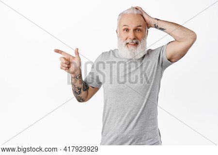 Surprised Old Guy Pointing Left And Touching Head, Smiling Amazed, Encounter Something Interesting,