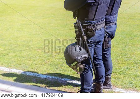 Two Riot Policemen Equipped With Different Protections On The Field Of A Soccer Field.