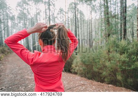 Runner woman getting ready to run pulling hair to do a ponytail preparing for long distance trail running in outdoor forest nature. Girl athlete from behind preparation for fitness workout motivation.