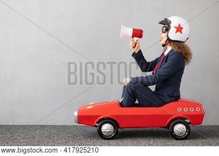 Successfull Businesswoman Driving Toy Car Outdoor