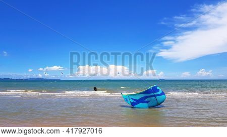 Blue Kite Surfing Falling Down On The Pattaya Beach With Sea, Cloud And Clear Blue Sky Background Wi