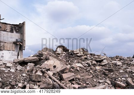 A Pile Of Concrete Wreckages Of Construction Debris Against The Background Of The Remains Of The Bui