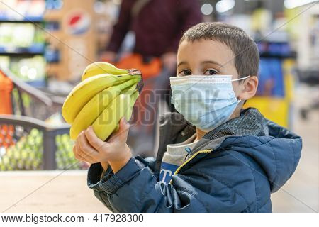 Child Wearing Surgical Face Mask Buying Fruit In Supermarket In Coronavirus Pandemic. Little Boy In