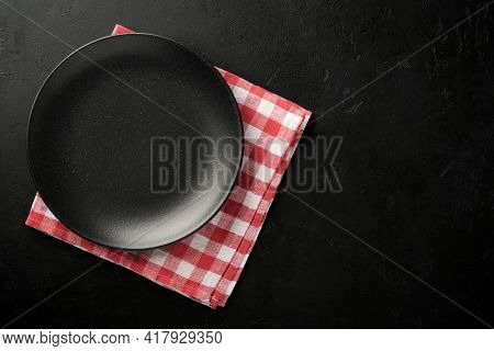 Black Empty Plate, Fork And Knife And Red Tablecloth. Kitchen Utensils Set On Black Stone Table. Top
