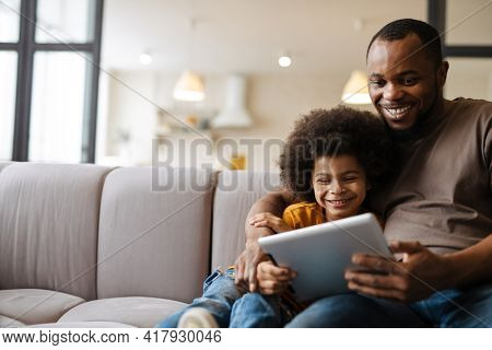 Black father and son smiling and using tablet computer while sitting on sofa at home