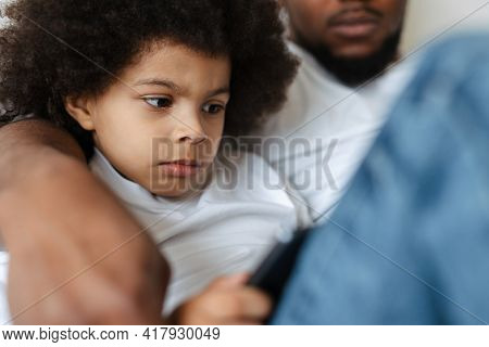 Black father and son using tablet computer while resting together at home