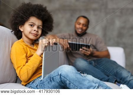 Black father and son smiling and using tablet computers while sitting on sofa at home