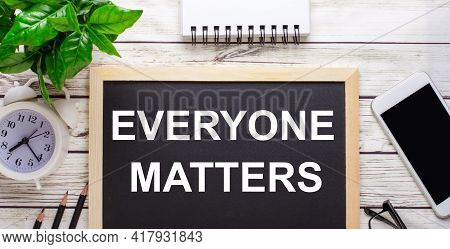 Everyone Matters Written On A Black Background Near Pencils, A Smartphone, A White Notepad And A Gre