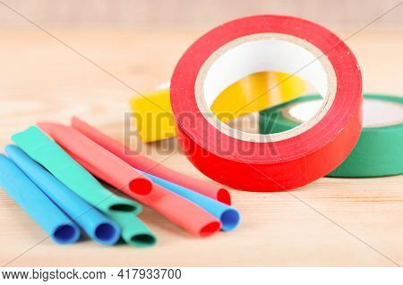 Colorful Electrical Insulating Tape And Heat Shrink Tubing Wooden Background