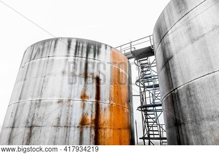 Old Fuel Oil Tanks With Fuel Oil Stains And Traces Of Rust At An Abandoned Industrial Plant.