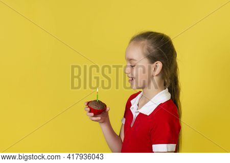 Teen Girl Blows Out A Candle On A Cupcake And Makes A Wish. Happy Birthday Or Make A Wish Concept. B
