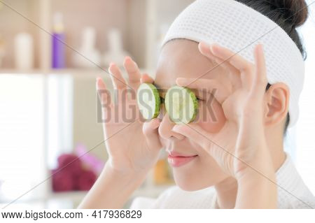 A Beautiful Asian Woman Uses Cucumber For Facial Treatment, Along With A Massage By A Professional M
