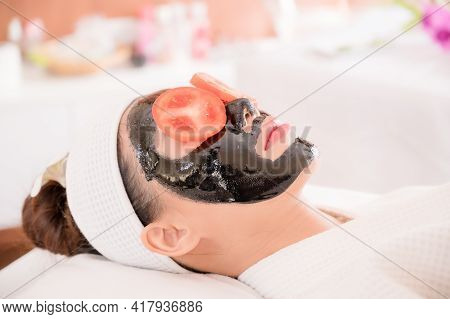 A Beautiful Asian Woman Uses Spa Mud And Tomato Slice For Facial Treatment