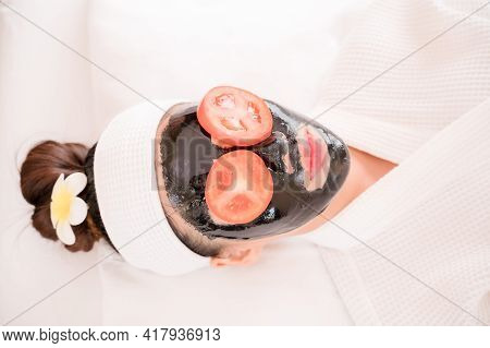 A Beautiful Asian Woman Uses Spa Mud And Tomato Slice For Facial Treatment, Along With A Massage By