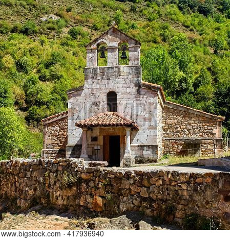 Small Stone Chapel Next To Ancient Stone Wall In The Green Field. Asturias.