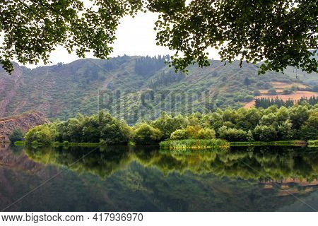 Reflections Of The Forest In The Calm Water On A Summer Day. Asturias. Spain.