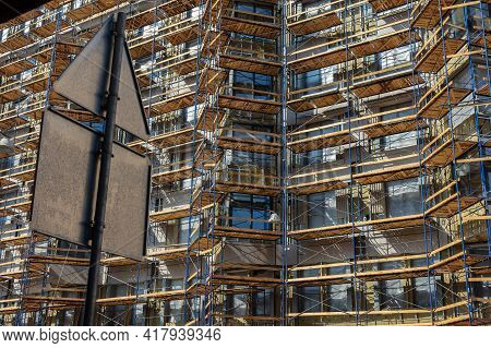 Tenement House In Scaffolding On The Building Facade. View From The City Street
