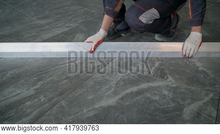 The Foreman Checks The Level Of The Laid Tiles On The Floor. A Worker In A Building Uniform Checks T