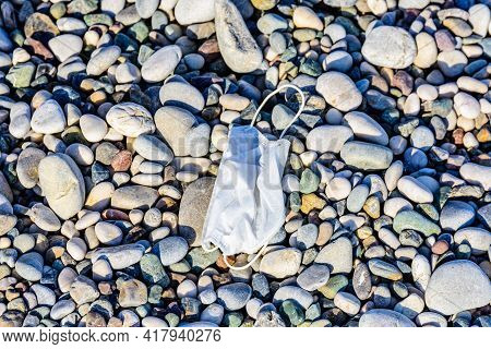 A Disposable Face Mask Discarded On Pebble At Beach