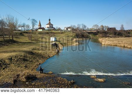 Man fishing in river Kamenka in Suzdal, nature of middle Russia, old Russian church in sunny day in spring middle april, Russian idyllic countryside, Golden Ring of Russia