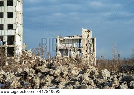 A Ruined Building Against A Blue Sky With Gray Clouds With A Pile Of Concrete Rubble In The Foregrou