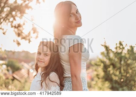 Mother And Daughter Standing Back To Back. Afternoon Light