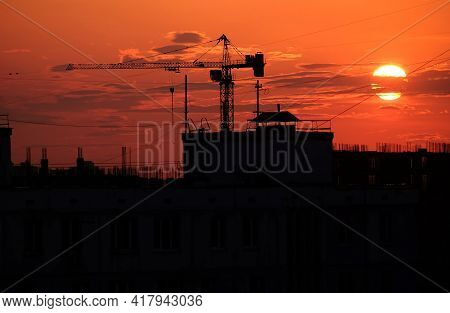 Contour Of Tower Crane Above The Constructing Buildings Against Evening Sky And The Red Beautiful Su
