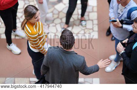 students communication with professor in school corridor