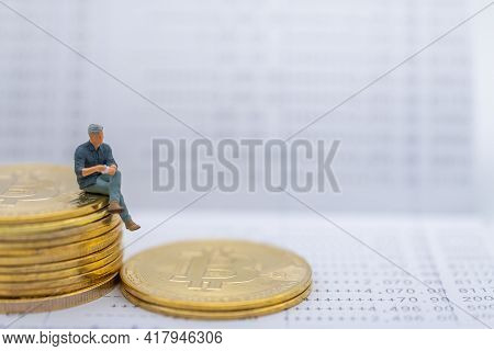 Business, Money, Cryptocurrency And Financial Concept. Businessman Miniature Figure Sitting On Stack