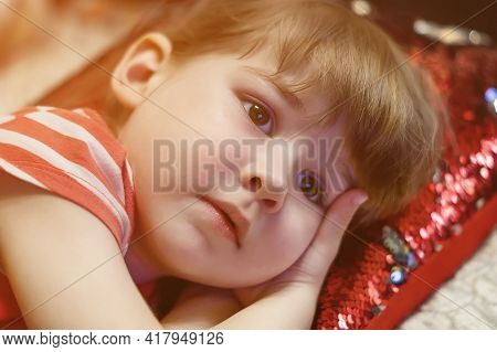 Beautiful Little Girl Lying Calmly On A Red Pillow, Close-up. Cute Baby Face. A Beautiful Portrait O