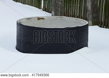 One Big Black Concrete Ring In A Snowdrift Of White Snow On A Winter Street
