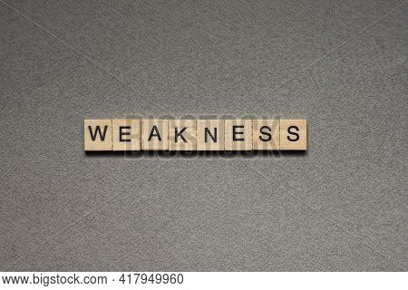 Text The Word Weakness From Brown Wooden Small Letters With Black Font On An Gray Table