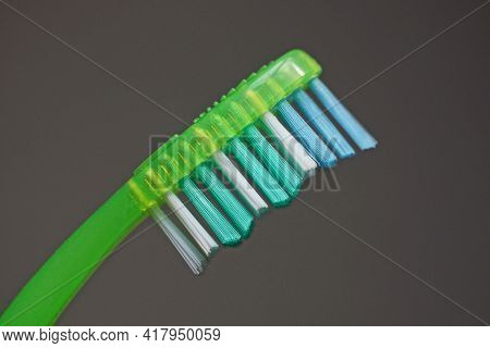 Part Of One Toothbrush With Colored Bristles On A Green Plastic Handle On A Gray Background