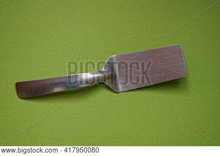 One Small Gray Metal Scoop Lies On A Green Table