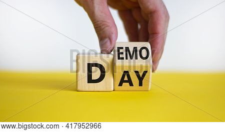 Demo Day Symbol. Businessman Turns A Cube And Changes The Word 'day' To 'demo'. Beautiful Yellow Tab