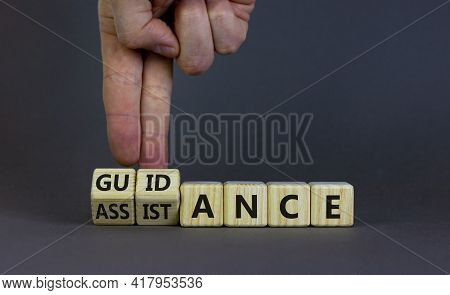 Guidance And Assistance Symbol. Businessman Turns Cubes, Changes Words 'assistance' To 'guidance'. B