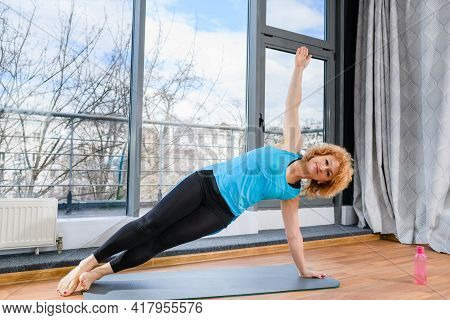 Blonde Curly Mature Woman Stay On Knees And Stretch Hands Up At Grey Floor Mat With Water Bottle, He