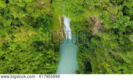 Aerial Top View Jungle Waterfall In A Tropical Forest Surrounded By Green Vegetation. Mantayupan Fal