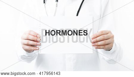 Notepad With Hormones Text In Doctor's Hands On White Background, Medical Concept