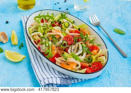 Healthy Salad With Fresh Vegetables, Shrimps And Squid In A White Oval Bowl On A Light Blue Concrete