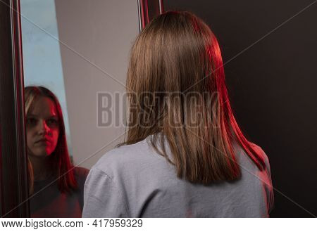 Young Woman Looking At Her Mirror Reflection With Grief. Unhappy Sad Person. Psychological Concept O