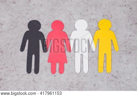 Four Figures Of People Holding Hands. Gray Background. Friendship Of Nations.