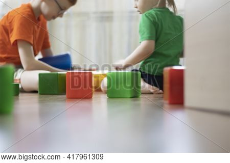 In The Foreground, The Cubes In Kindergarten And In The Background Are Out Of Focus Children Who Pla