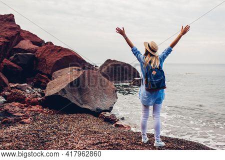 Woman Traveler Walking Raised Arms Feeling Happy On Red Beach In Santorini Island, Greece. Tourist A