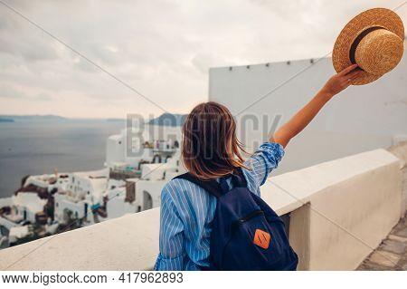 Tourist Woman Walking On Santorini Island, Greece Enjoying Sea And City Architecture Landscape. Trav
