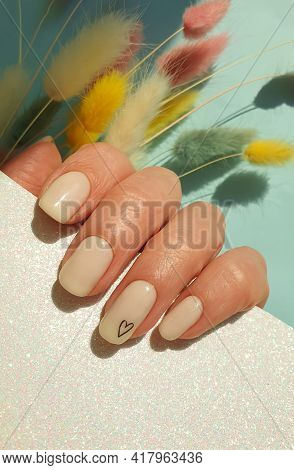 Female Hand Beautiful Beige Manicure On A Colored Background