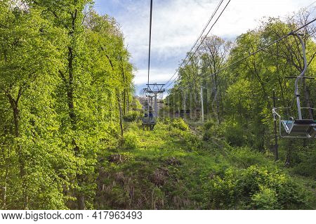 Chairlift In The Mountains. Ascent On A Cableway Among Green Trees. Tourist Mountain Resort. Spring