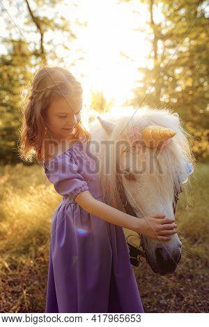Girl In Purple Dress Hugging White Unicorn Horse. Dreams Come Tr